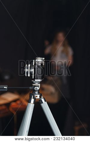 The Old Camera On The Tripod Stands In The Room Into Which The Girl Enters
