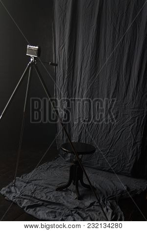 The Old Camera On The Tripod Stands In The Room On Black Background