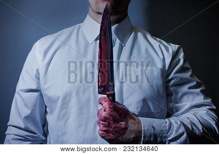 Horror Photo Of A Scary Killer Posing With A Sharp And Bloody Big Kitchen Knife.