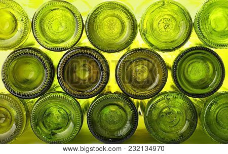 Close Up Stack Of Many Empty Washed Green Glass Wine Bottles Bottom Side, Low Angle View