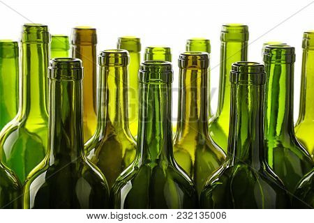 Close Up Group Of Many Empty Washed Green Glass Wine Bottles In A Row Isolated On White Background,