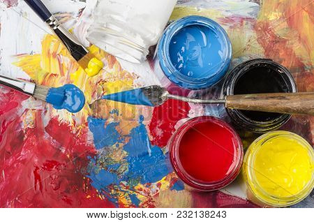 Glass Jars With Acrylic Primary Colors And A Dirty Palette With A Spatula And Brushes