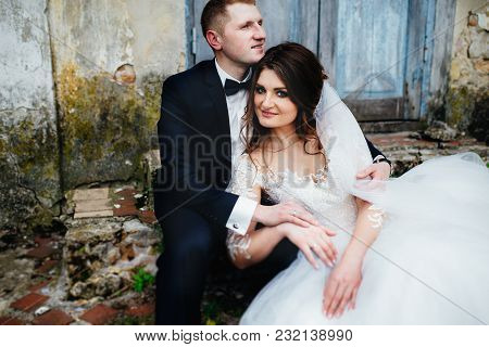 Fashionable Wedding Couple Sitting Near Old House And Smiling. Husband Holding His Wife. Bride Weari