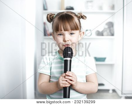 Cute Little Girl Singing Karaoke At Home. Selected Focus. Toned.