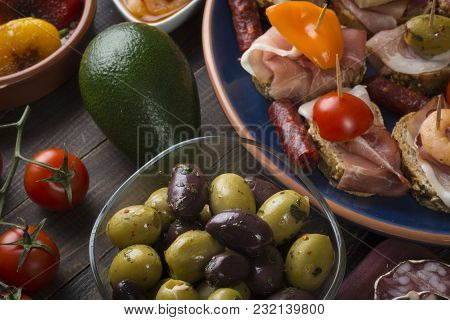Sharing Mixed Spanish Tapas Food Starters With Olives, Salami Sausage And Sandwiches On Vintage Old
