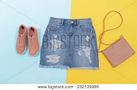 Jeans shorts with shoes,hanbag isolated on blue and yellow background