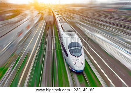 High-speed Passenger Train Travels At High Speed Railroad Green Grass. Top View With Motion Effect,