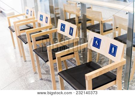 Four Wooden Chairs At The Airport With Signs For The Disabled And The Elderly. Allocation Of Public