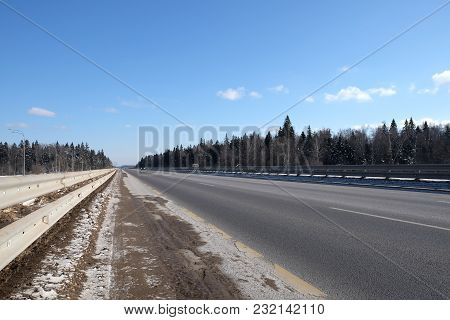 Landscape With Long Straight Suburban Highway With Metal A Fence On The Sides And Forest Under Clear