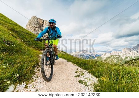Tourist cycling in Cortina d'Ampezzo, stunning Cinque Torri and Tofana in background. Man riding MTB enduro flow trail. South Tyrol province of Italy, Dolomites.