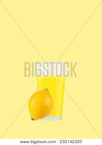 Fresh Lemon Juice And Lemon Near Glass On Pastel Yellow Background