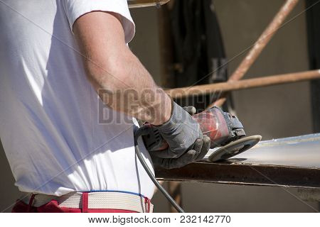 Worker Renovating Metal Plate With Angle Grinder
