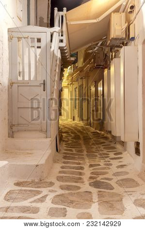 Narrow Traditional Street In The City Of Chora At Night. Island Mykonos. Greece.