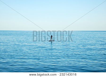 Lonely Girl Floating On A Sup Board In The Open Sea
