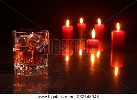 Christmas Decoration. Glass Of Cognac Or Whiskey And Red Candle On A Wooden Background