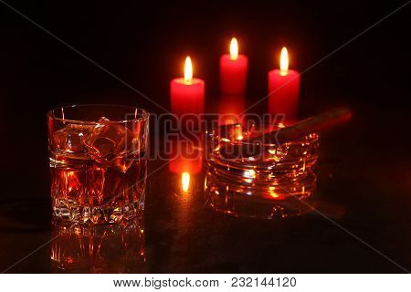 Glass Of Cognac Or Whiskey, Cigar And Red Candles On A Wooden Background. Christmas Decoration