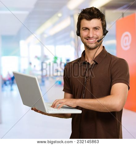 Man With Microphone Holding Laptop, Indoors