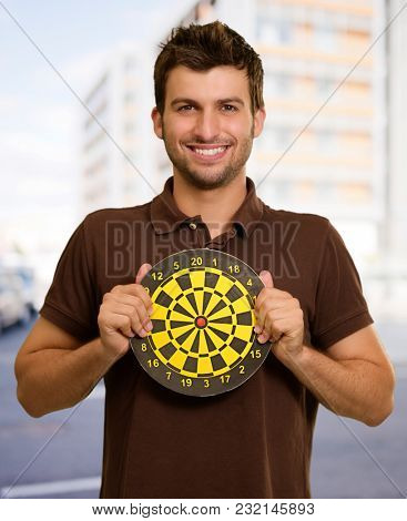 Portrait Of A Man Holding A Dartboard, Outdoors