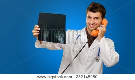 Doctor Holding X-ray While Talking On Phone On Blue Background
