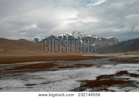 A View Including The Mountains, Creek And Dunes Of, Great Sand Dunes National Park And Preserve.