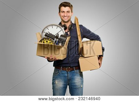 Happy Young Man Holding Cardboxes On Grey Background