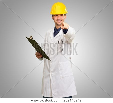 Young Architect Holding Clipboard And Pointing On Grey Background