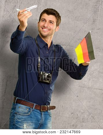 Photographer Holding German Flag And Miniature Airplane, Indoor