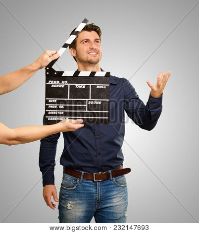 Director Clapping The Clapper Board On Grey Background