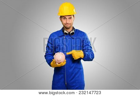 Engineer Holding Piggy Bank On Grey Background