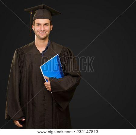 Happy Graduate Man Holding Book On Black Background