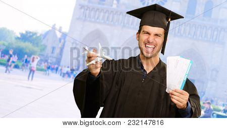 Graduate Man Holding Miniature Airplane And Boarding Pass, Outdoors