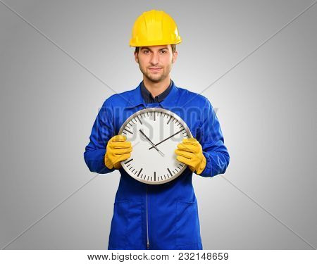 Engineer Holding Wall Clock Isolated On Grey Background