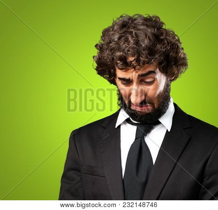 Portrait Of An Unhappy Businessman against a green background