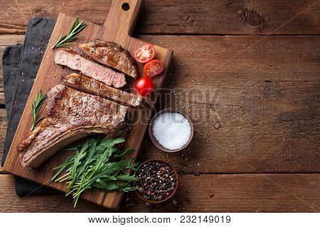 Grilled Cowboy Beef Steak, Herbs And Spices On A Rustic Wooden Background. Top View With Copy Space