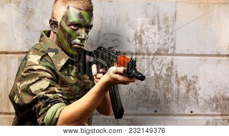 Portrait Of A Soldier Aiming With Gun against an old rusty wall