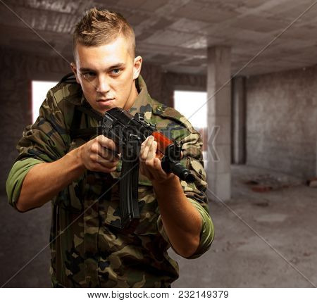 Portrait Of A Soldier Aiming With Gun in an old building