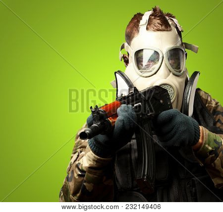 Portrait Of A Soldier With Gas Mask Aiming With Gun against a green background