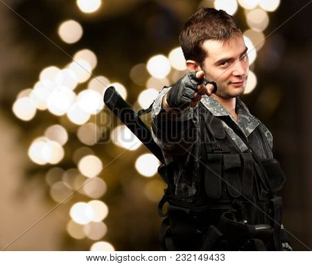Portrait Of A Soldier Pointing against a background of shiny lights