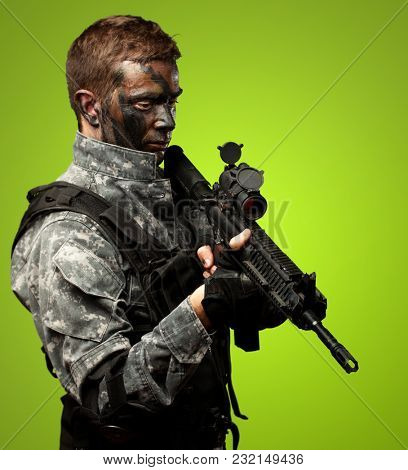 Portrait Of Soldier Holding Gun against a green background