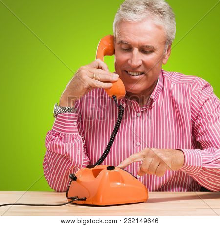 Mature Man Talking On Telephone against a green background