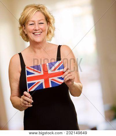 Happy Mature Woman Holding British Flag, Indoors