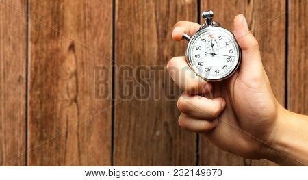 Close Up Of Hand Holding Stopwatch against a wooden background
