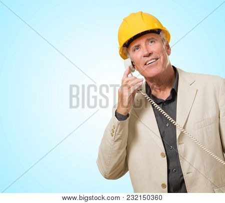 Architect Man Talking On Telephone against a blue background