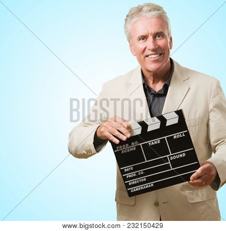 Mature Man Holding Clapper Board against a blue background