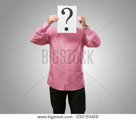 Man Hiding His Face Behind Question Mark On Gray Background