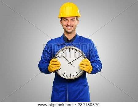 Happy Engineer Holding Wall Clock Isolated On Grey Background