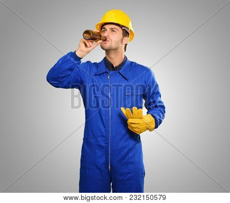 Portrait Of Thirsty Engineer Isolated On Grey Background
