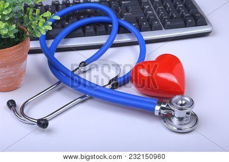 Stethoscope On Modern Laptop Computer. Red Heart On White Table With Space For Text. Healthcare Conc