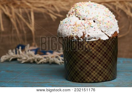 Kulichi, Traditional Russian Easter Cake With Icing On Rustic Wooden Table With Straw On Background