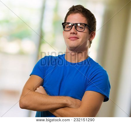 Young man wearing eyeglasses with his arms crossed against an abstract background